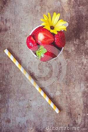 Top view of strawberries in a white cup and a yellow stripped straw on wooden background