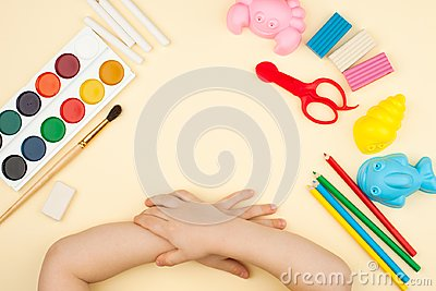 stock image of the child sits at the table with objects for creativity, drawing and hobbies, the top view.