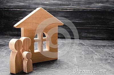 Wooden figures of the family stand near a wooden house. The concept of finding a new home, moving. A healthy strong family