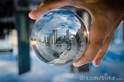 Cityscape photography in a clear glass crystal ball with dramatic clouds sky.