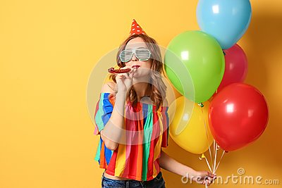 Young woman with balloons and party blower on color background. Birthday celebration