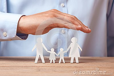 stock image of medical or travel insurance. man covers the family with his hands from his father, mother, son and daughter