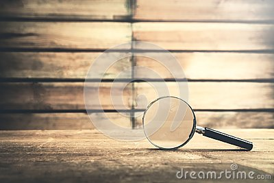 Magnifying glass on wooden table. Search and discover