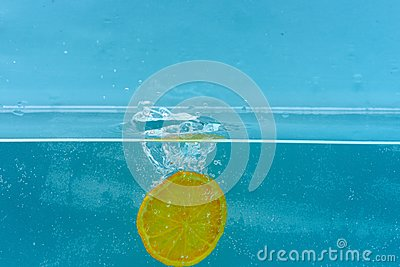 Slice of orange under water with transparent bubbles and water drops splashes. Fruit fall into water, blue background