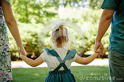 Family, parenthood, adoption and people concept. happy mother, father and little girl walking in summer park