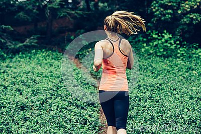 stock image of caucasian woman running on forest trail wearing sport clothes