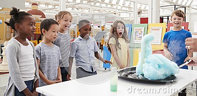 stock image of kids having fun watching an experiment at a science centre