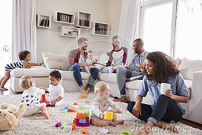Friends with toddlers playing on the floor in sitting room