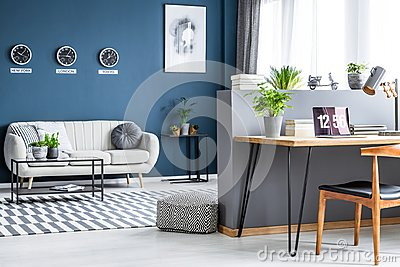Dark blue living room interior with three clocks, simple poster, bright sofa and home office corner with laptop on hairpin desk
