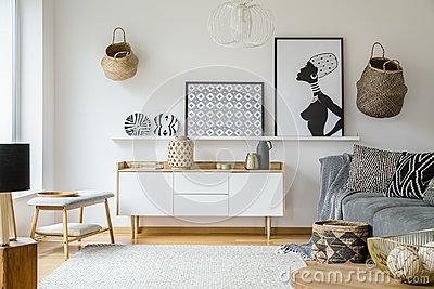 Posters and plates above wooden cupboard in boho living room int