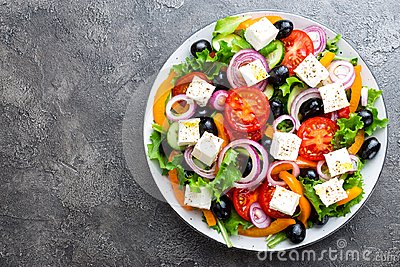 Greek salad. Fresh vegetable salad with tomato, onion, cucumbers, pepper, olives, lettuce and feta cheese. Greek salad