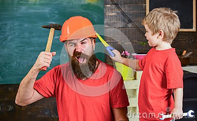 Fatherhood concept. Father, parent with beard in protective helmet teaching little son to use different tools in school