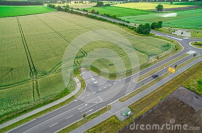 Aerial view of a road with signs and guidelines for traffic between a new development area for an industrial estate and an arable