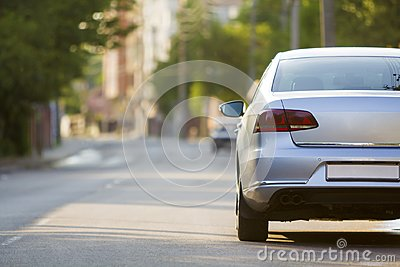 Close-up back view of new shiny expensive silver car moving along city street on blurred trees, cars and buildings background on