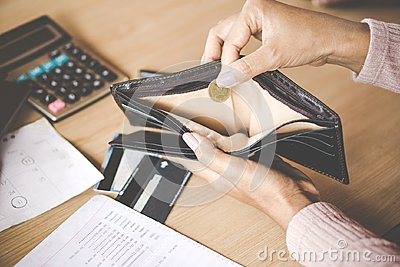 Woman hand holding one coin bankrupt broke after credit card payday