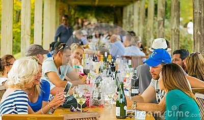 stock image of crowds of people sitting at dining area of wine event