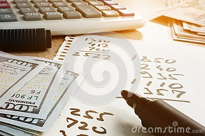 Home finances. Paper with calculations, calculator and money.