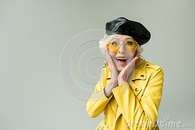 stylish excited senior woman in yellow jacket and leather beret,