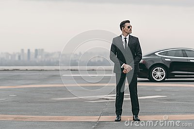 serious bodyguard standing with sunglasses and security earpiece on helipad and looking