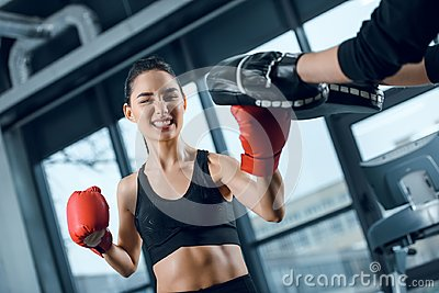 expressive young female boxer exercising with trainer
