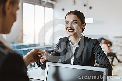attractive young businesswoman giving passport and ticket to staff at airport check