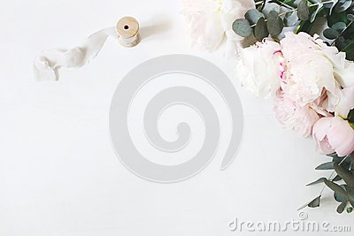Feminine wedding or birthday table composition with floral bouquet. White and pink peonies flowers, eucalyptus and silk