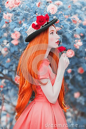 Young redhead girl feels a bright sense from the smell of flower in garden. Very long hair. Bright rose background