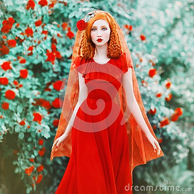 Young beautiful redhead girl with very long hair braided in plait. Fabulous renaissance woman in a red dress against the backdrop