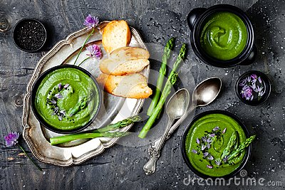 Homemade green spring asparagus cream soup decorated with black sesame seeds and edible chives flowers.