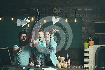 American family at desk with son play with paper planes. Homeschooling concept. Kid with parents in classroom with usa