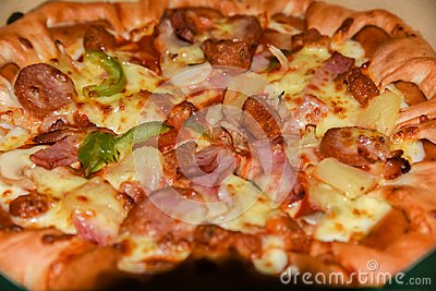stock image of pizza in a cardboard box against a wood background. pizza menu. food ingredients and spices for cooking mushrooms, tomatoes, chee