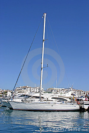 Luxury white yacht with tall mast and reflection in calm port in Spain with sun and blue sky