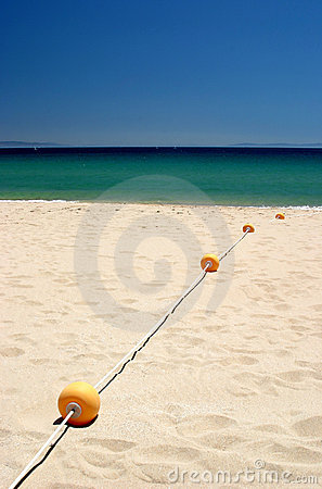 String of yellow buoys on sunny, sandy beach