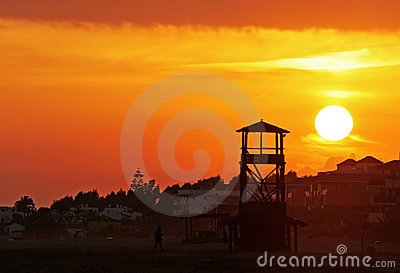 Huge glowing golden sun sets behind a wooden lookout tower on a beautiful sandy beach in Spain