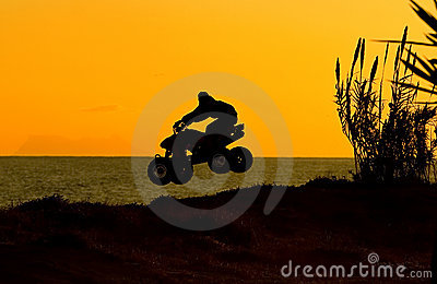 Silouette of quad bike jumping