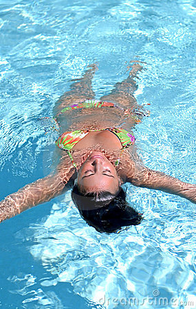 Attractive, fit woman floating in swimming pool