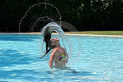Girl or woman in swimming pool throwing wet hair back