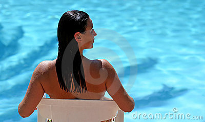 Attractive woman by blue sunny swimming pool