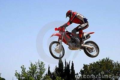 Moto X Motorbike jumping through the air on a hot sunny day with big blue sky