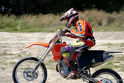 Speeding Moto X bike Rider with blurred background as he rushes past on dirt track