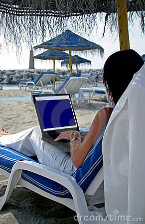 Business woman working on a laptop on the beach