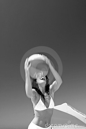 Girl catching beach ball on sunny beach in Spain. Black and white.