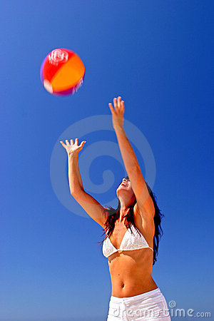 Girl catching beach ball on sunny beach in Spain with blue sky