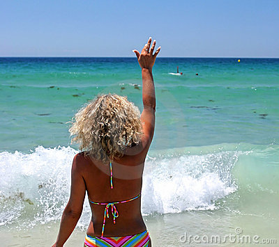 Woman in bikini on white beach waving to her husband