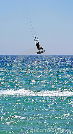 Kitesurfer flying high through the air as his kite hits some serious wind.