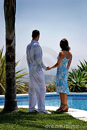Young attractive couple in love holding hands under a palm tree