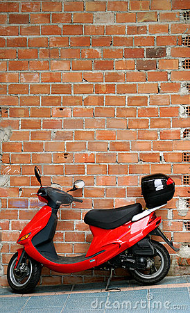 Red moped or motorbike resting or leaning against a brick wall.