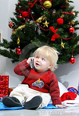 Young boy talking on mobile phone under a christmas tree.