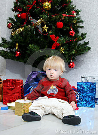 Young boy or toddler under a christmas tree