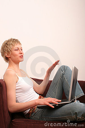 Happy woman with laptop is talking to somebody